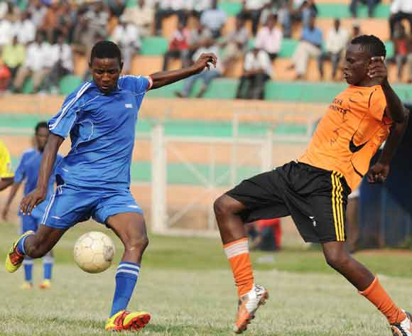 Samuel Oguti (L) and John Muwanguzi (R) of Soana FC challenge Ayub Kisalita (C) of SC Villa during the 2014 Fufa Super League at Nakivubo Stadium, Kampala on 07 February 2014 ©Ismail Kezaala/BackpagePix