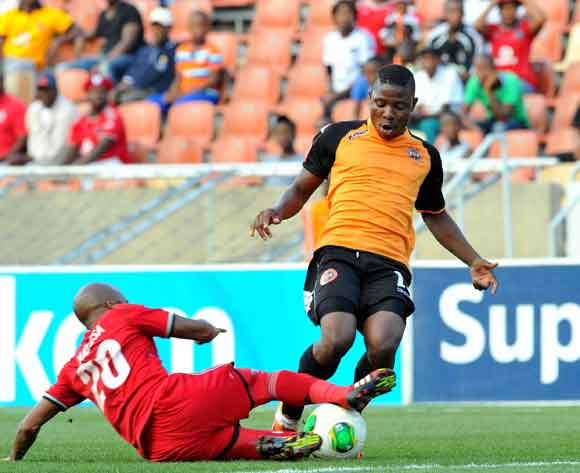 Puleng Tlolane of Polokwane City tackled by Oupa Manyisa of Orlando Pirates during the Absa Premiership football match between Polokwane City and Orlando Pirates at the Peter Mokaba Stadium, Limpopo on the 15 February 2014 ©Samuel Shivambu/BackpagePix