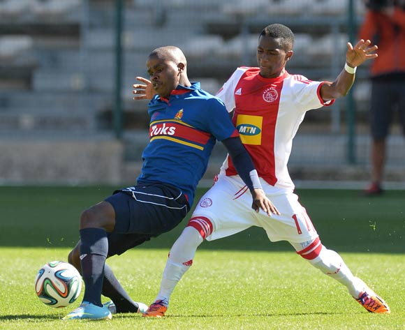 Telinho of Ajax Cape Town battles for the ball with Junior Sibande of University of Pretoria during the Absa Premiership 2013/14 football match between Ajax Cape Town and University of Pretoria at Athlone Stadium, Cape Town on 16 March 2014