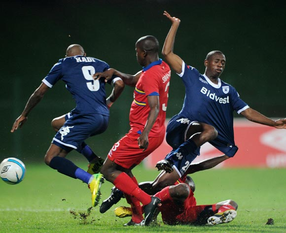 Siyabonga Nhlapho and Calvin Kadi of Bidvest Wits battles with Junior Sibande of University Pretoria during theAbsa Premiership 2013/14 match between University of Pretoria and Bidvest Wits at Tuks Stadium in Pretoria on the 19 March 2014
