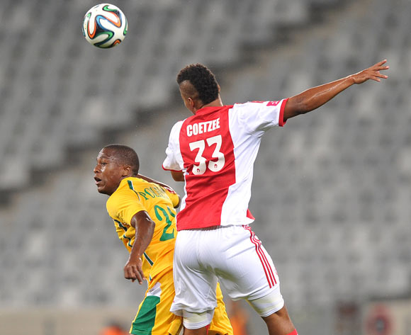 Rivaldo Coetzee of Ajax Cape Town wins the aerial battle with Kgotso Polelo of Golden Arrows during the Absa Premiership 2013/14 game between Ajax Cape Town and Golden Arrows at Cape Town Stadium, Cape Town on 9 April 2014