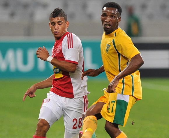 Vuyisile Ntombaythethi of Golden Arrows  gets his pass away ahead of Keagan Dolly of Ajax Cape Town during the Absa Premiership 2013/14 game between Ajax Cape Town and Golden Arrows at Cape Town Stadium, Cape Town on 9 April 2014
