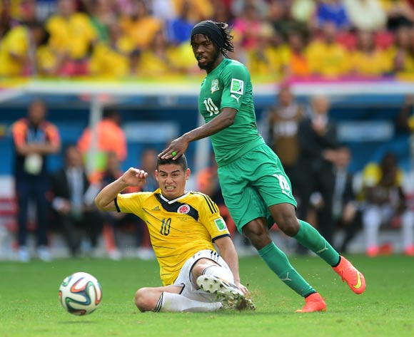 Colombia's James Rodriguez battles for the ball with Ivory Coast's Gervinho
