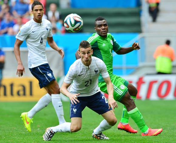 Laurent Koscielny of France heads away from Emmanuel Emenike of Nigeria  during the 2014 Brazil World Cup Final Last 16 football match between France and Nigeria at the Estadio Nacional Brasilia, Brazil on 30 June 2014