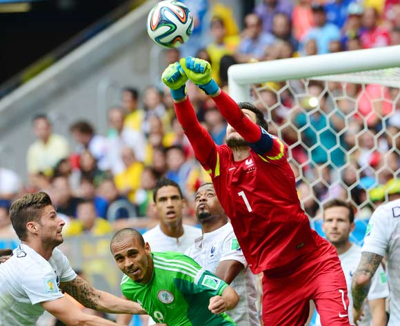 Hugo Lloris of France punches clear from Peter Odemwingie of Nigeria and teammate Olivier Giroud (l) during the 2014 Brazil World Cup Final Last 16 football match between France and Nigeria at the Estadio Nacional Brasilia, Brazil on 30 June 2014