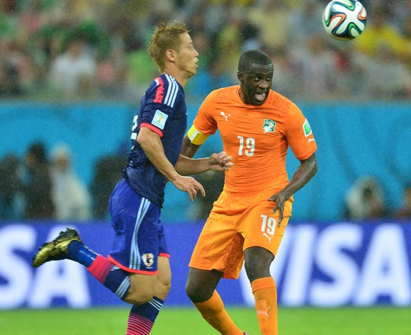 Yaya Toure of Ivory Coast heads ball past Keisuke Honda of Japan during the 2014 Brazil World Cup Finals, Group C, football match between Ivory Coast and Japan at the Arena Pernambuco in Recife, Brazil on 14 June 2014