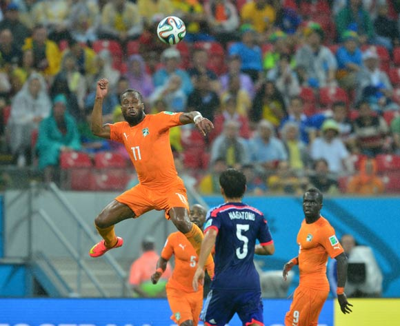 Didier Drogba of Ivory Coast climbs high to head the ball as Yuto Nagatomo of Japan watches on during the 2014 Brazil World Cup Finals, Group C, football match between Ivory Coast and Japan at the Arena Pernambuco in Recife, Brazil on 14 June 2014