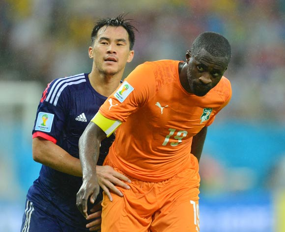 Yaya Toure of Ivory Coast held back by Shinji Okazaki of Japan during the 2014 Brazil World Cup Finals, Group C, football match between Ivory Coast and Japan at the Arena Pernambuco in Recife, Brazil on 14 June 2014