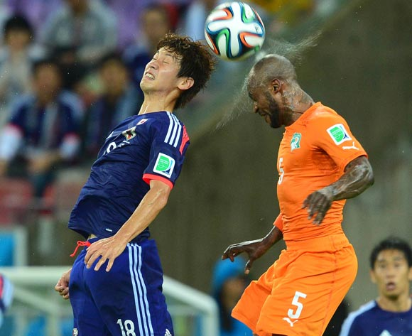Yuya Osako of Japan challenged by Didier Zokora of Ivory Coast during the 2014 Brazil World Cup Finals, Group C, football match between Ivory Coast and Japan at the Arena Pernambuco in Recife, Brazil on 14 June 2014