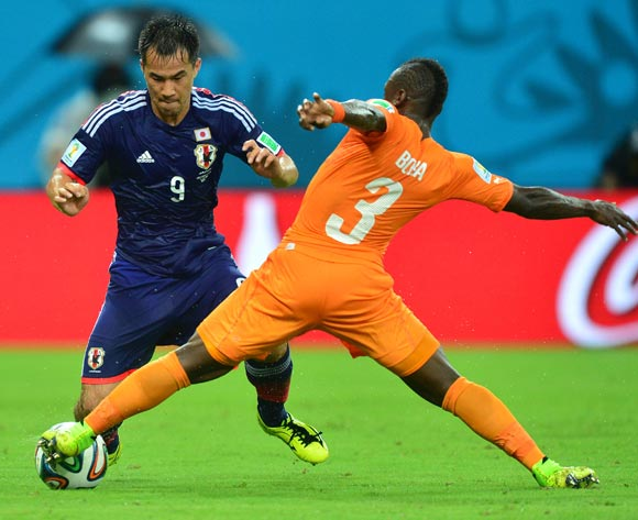 Arthur Boka of Ivory Coast tackles Shinji Okazaki of Japan  during the 2014 Brazil World Cup Finals, Group C, football match between Ivory Coast and Japan at the Arena Pernambuco in Recife, Brazil on 14 June 2014