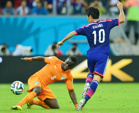 Ismael Tiote of Ivory Coast tackles Shinji Kagawa of Japan  during the 2014 Brazil World Cup Finals, Group C, football match between Ivory Coast and Japan at the Arena Pernambuco in Recife, Brazil on 14 June 2014