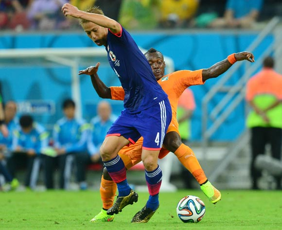 Keisuke Honda of Japan tackled by Arthur Boka of Ivory Coast  during the 2014 Brazil World Cup Finals, Group C, football match between Ivory Coast and Japan at the Arena Pernambuco in Recife, Brazil on 14 June 2014