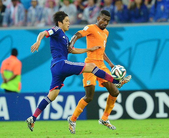 Atsuto Uchida of Japan tackles Salomon Kalou of Ivory Coast  during the 2014 Brazil World Cup Finals, Group C, football match between Ivory Coast and Japan at the Arena Pernambuco in Recife, Brazil on 14 June 2014 ©Gavin Barker/BackpagePix