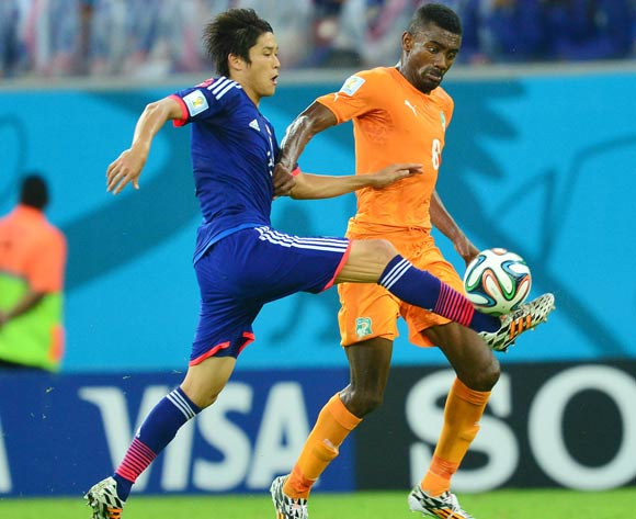 Atsuto Uchida of Japan tackles Salomon Kalou of Ivory Coast  during the 2014 Brazil World Cup Finals, Group C, football match between Ivory Coast and Japan at the Arena Pernambuco in Recife, Brazil on 14 June 2014