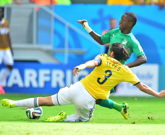 Mario Yepes of Colombia tackles Max Gradel of Ivory Coast  during the 2014 Brazil World Cup Final Group C football match between Colombia and Ivory Coast at the Estadio Nacional Brasilia, Brazil on 19 June 2014