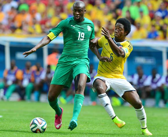Yaya Toure of Ivory Coast shields ball from Carlos Sanchez of Colombia during the 2014 Brazil World Cup Final Group C football match between Colombia and Ivory Coast at the Estadio Nacional Brasilia, Brazil on 19 June 2014