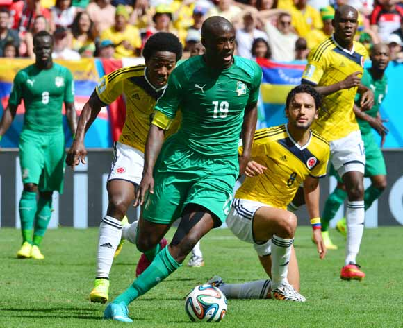 Yaya Toure of Ivory Coast evades tackle from Carlos Sanchez of Colombia during the 2014 Brazil World Cup Final Group C football match between Colombia and Ivory Coast at the Estadio Nacional Brasilia, Brazil on 19 June 2014