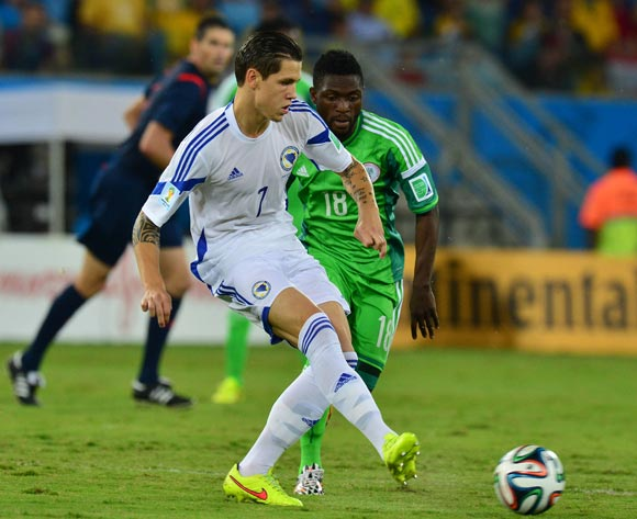 Muhamed Besic of Bosnia and Herzegovina clears from Michael Babatunde of Nigeria during the 2014 Brazil World Cup Final Group F football match between Nigeria and Bosnia at the Arena Pantanal in Cuiaba, Brazil on 21 June 2014
