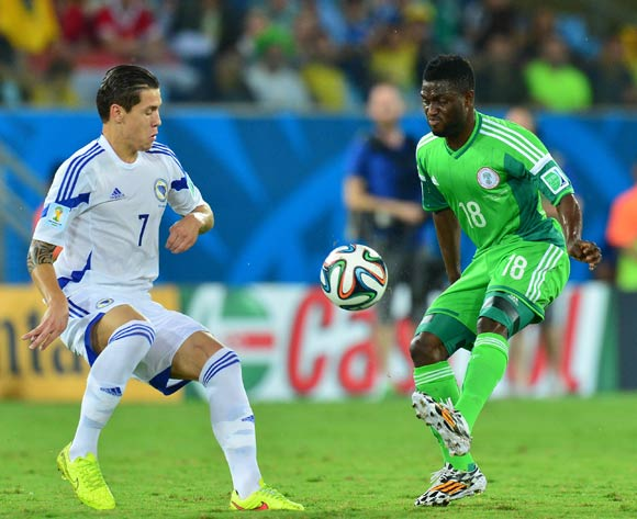 Michael Babatunde of Nigeria clears from Muhamed Besic of Bosnia and Herzegovina during the 2014 Brazil World Cup Final Group F football match between Nigeria and Bosnia at the Arena Pantanal in Cuiaba, Brazil on 21 June 2014