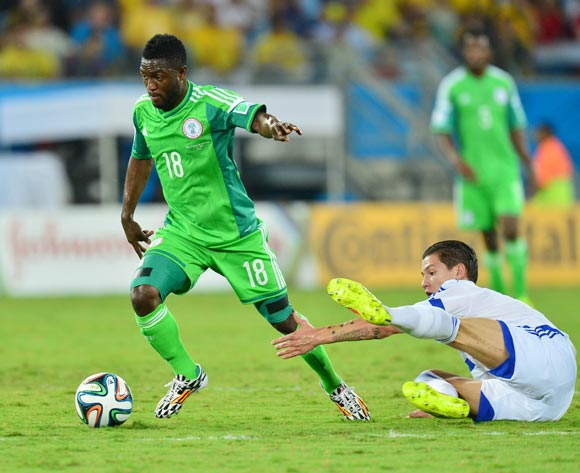 Michael Babatunde of Nigeria evades challenge from Muhamed Besic of Bosnia and Herzegovina  during the 2014 Brazil World Cup Final Group F football match between Nigeria and Bosnia at the Arena Pantanal in Cuiaba, Brazil on 21 June 2014