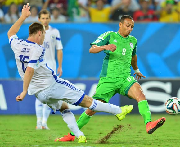 Peter Odemwingie of Nigeria challenges Toni Sunjic of Bosnia and Herzegovina during the 2014 Brazil World Cup Final Group F football match between Nigeria and Bosnia at the Arena Pantanal in Cuiaba, Brazil on 21 June 2014