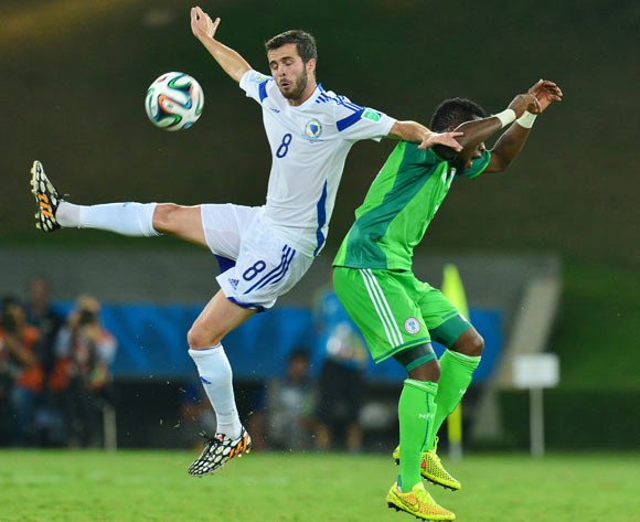 Zvjezdan Misimovic of Bosnia and Herzegovina and Ogenyi Onazi of Nigeria  during the 2014 Brazil World Cup Final Group F football match between Nigeria and Bosnia at the Arena Pantanal in Cuiaba, Brazil on 21 June 2014