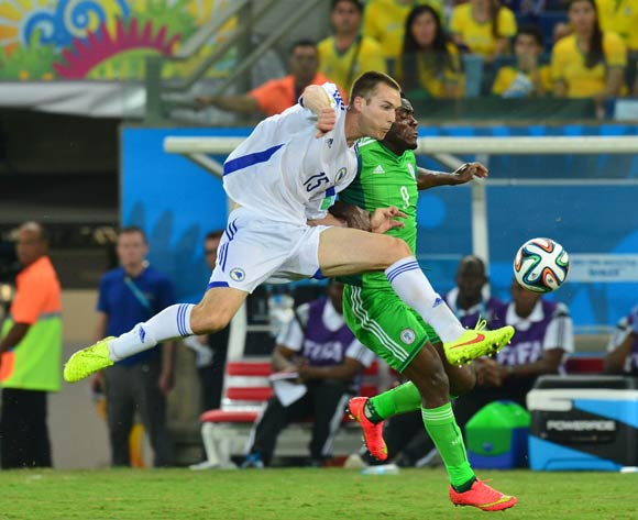 Toni Sunjic of Bosnia and Herzegovina clears from Emmanuel Emenike of Nigeria  during the 2014 Brazil World Cup Final Group F football match between Nigeria and Bosnia at the Arena Pantanal in Cuiaba, Brazil on 21 June 2014
