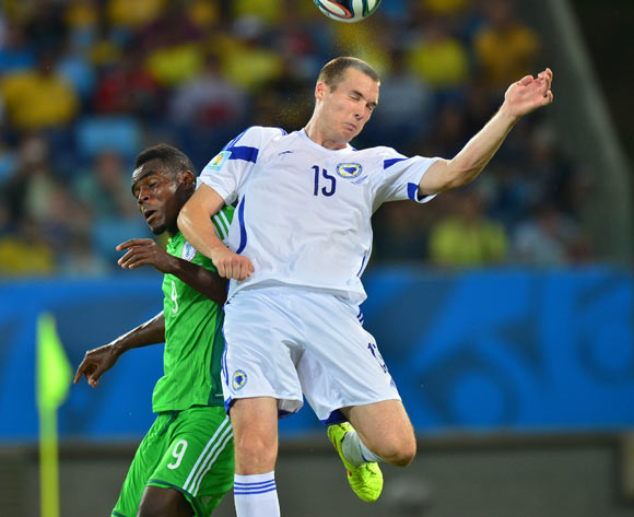 Toni Sunjic of Bosnia and Herzegovina heads ball clear from Emmanuel Emenike of Nigeria during the 2014 Brazil World Cup Final Group F football match between Nigeria and Bosnia at the Arena Pantanal in Cuiaba, Brazil on 21 June 2014