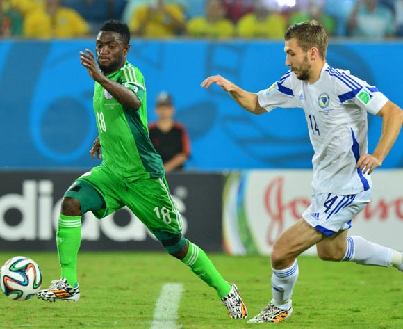 Michael Babatunde of Nigeria evades challenge from Tino Sven Susic of Bosnia and Herzegovina during the 2014 Brazil World Cup Final Group F football match between Nigeria and Bosnia at the Arena Pantanal in Cuiaba, Brazil on 21 June 2014