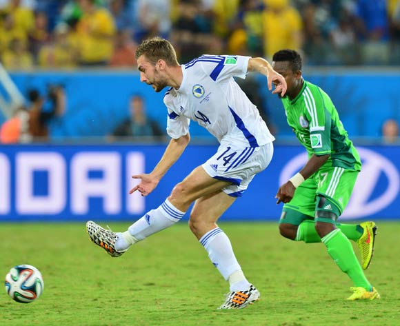 Tino Sven Susic of Bosnia and Herzegovina clears from Ogenyi Onazi of Nigeria during the 2014 Brazil World Cup Final Group F football match between Nigeria and Bosnia at the Arena Pantanal in Cuiaba, Brazil on 21 June 2014