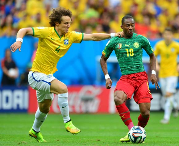 Eyong Enoh of Cameroon held back by David Luiz of Brazil during the 2014 Brazil World Cup Final Group A football match between Cameroon and Brazil at the Estadio Nacional Brasilia, Brazil on 23 June 2014