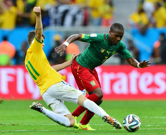 Oscar of Brazil tackles Landry Nguemo of Cameroon During the 2014 Brazil World Cup Final Group A football match between Cameroon and Brazil at the Estadio Nacional Brasilia, Brazil on 23 June 2014
