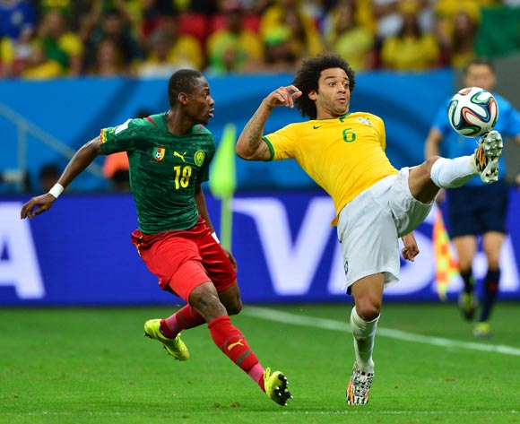 Marcelo of Brazil controls ball away from Eyong Enoh of Cameroon during the 2014 Brazil World Cup Final Group A football match between Cameroon and Brazil at the Estadio Nacional Brasilia, Brazil on 23 June 2014