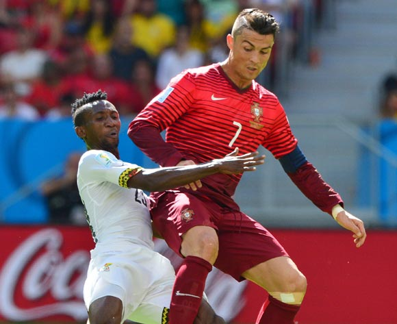 Harrison Afful of Ghana tackles Cristiano Ronaldo of Portugal during the 2014 Brazil World Cup Final Group G football match between Portugal and Ghana at the Estadio Nacional Brasilia, Brazil on 26 June 2014