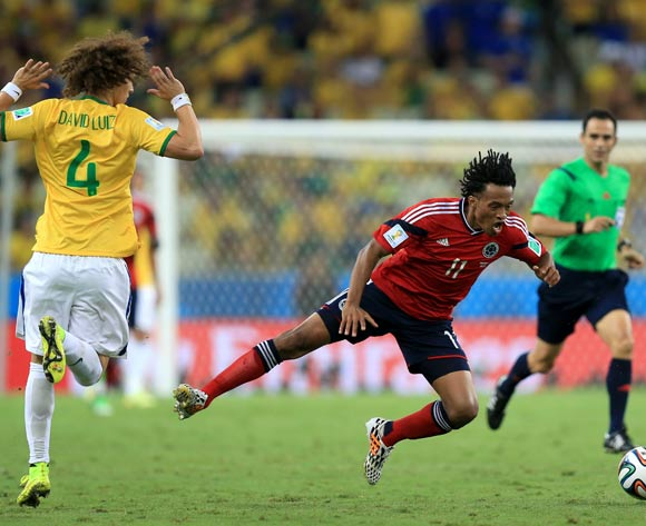 Colombia's Juan Cuadrado (right) goes down under the challenge from Brazil's David Luiz (left) during the quarter final match at the Estadio Castelao, Fortaleza.