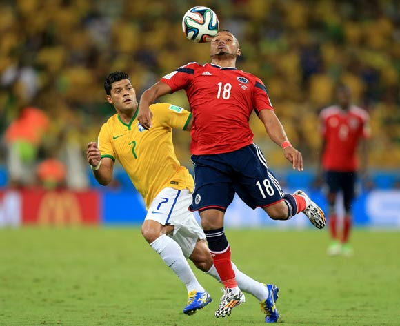 Colombia's Juan Camilo Zuniga (right) chests the ball away from Brazil's Hulk (left) during the quarter final match at the Estadio Castelao, Fortaleza.