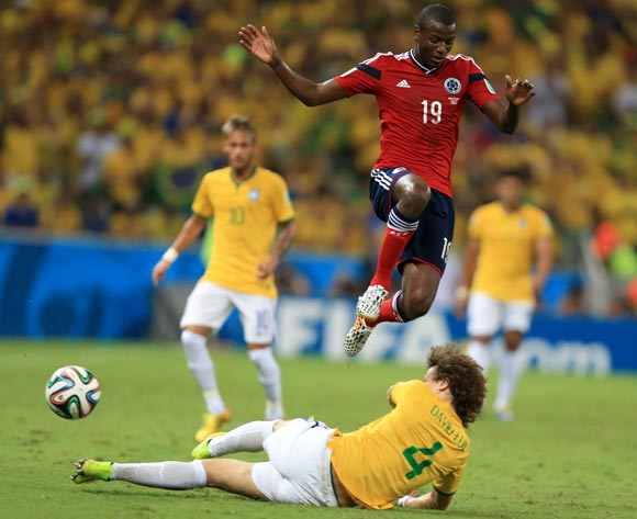 Colombia's Adrian Ramos (top) and Brazil's David Luiz battle for the ball during the quarter final match at the Estadio Castelao, Fortaleza
