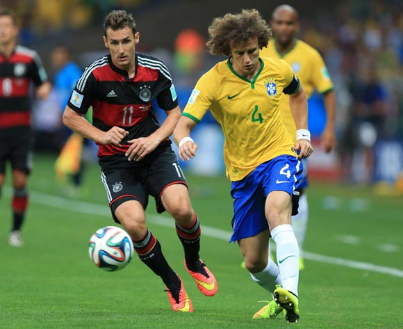 Brazil's David Luiz passes the ball away from Germany's Miroslav Klose (left) during the FIFA World Cup Semi Final at Estadio Mineirao, Belo Horizonte, Brazil.