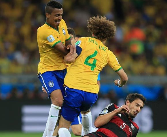 Brazil's Luis Gustavo (left) and David Luis (4) battle for the ball with Germany's Mats Hummels (right) during the FIFA World Cup Semi Final at Estadio Mineirao, Belo Horizonte, Brazil.