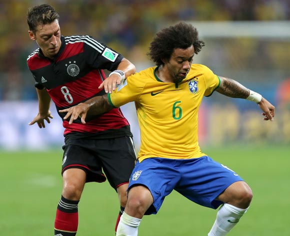 Brazil's Marcelo (right) and Germany's Mesut Ozil battle for the ball during the FIFA World Cup Semi Final at Estadio Mineirao, Belo Horizonte, Brazil