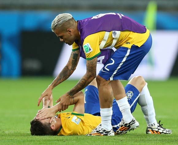 Brazil's Oscar (on floor) has to be consoled by teammate Dani Alves as he shows emotion after the final whistle during the FIFA World Cup Semi Final at Estadio Mineirao, Belo Horizonte, Brazil.