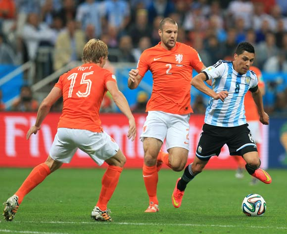 Argentina's Enzo Perez (right) looks to get past Netherlands' Dirk Kuyt (left) and Ron Vlaar during the FIFA World Cup Semi Final at the Arena de Sao Paulo, Sao Paulo, Brazil.