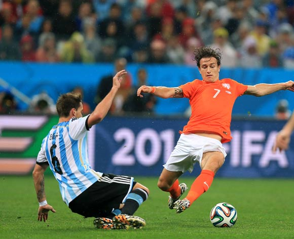 Netherlands' Daryl Janmaat (centre) dives in to challenge Argentina's Lucas Biglia (left) to concede a foul during the FIFA World Cup Semi Final at the Arena de Sao Paulo, Sao Paulo, Brazil