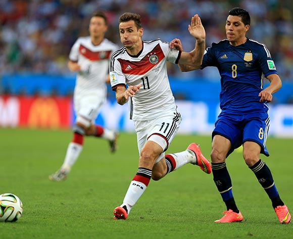 Germany's Miroslav Klose battles for the ball with Argentina's Enzo Perez (right) during the FIFA World Cup Final at the Estadio do Maracana, Rio de Janerio, Brazil.