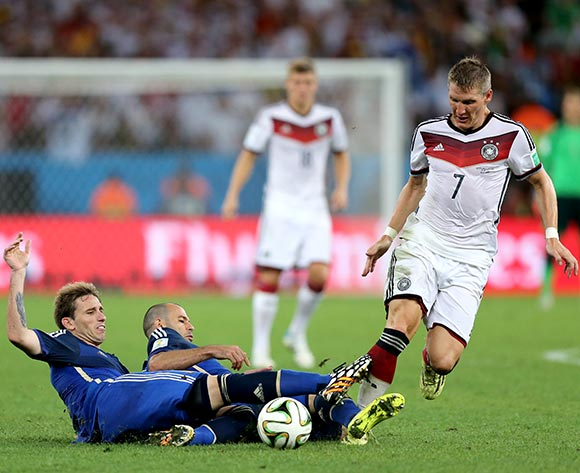 Germany's Bastian Schweinsteiger (right) is tackled by Argentina's  Lucas Biglia (left) and Javier Mascherano