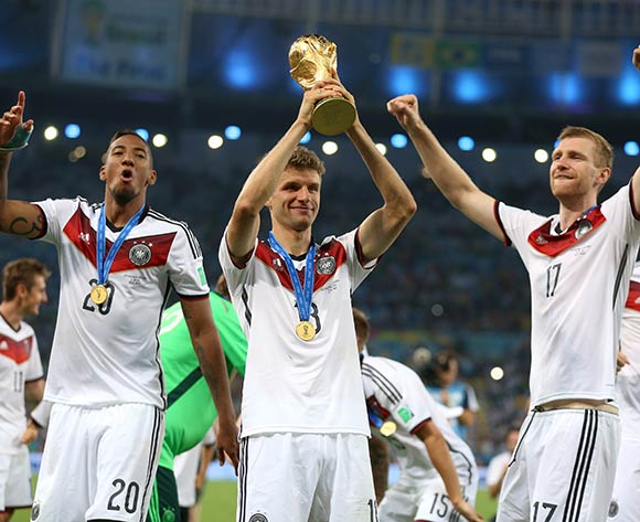 Germany's Thomas Muller celebrates with the World Cup and team-mates Jerome Boateng and Per Mertesacker after the FIFA World Cup Final at the Estadio do Maracana, Rio de Janerio, Brazil.