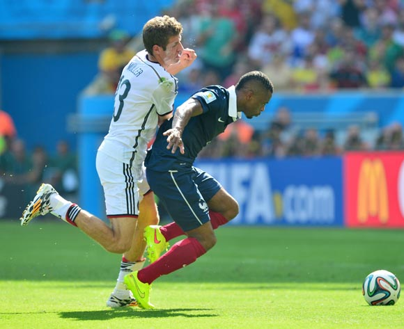 Thomas Muller of Germany challenges Patrice Evra of France during the 2014 Brazil World Cup Final Quarterfinal football match between France and Germany at the Maracana Stadium in Rio De Janeiro on 4 July 2014