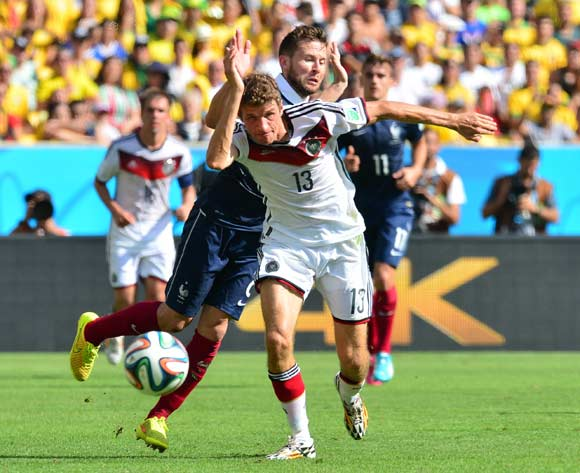 Thomas Muller of Germany held back by Yohan Cabaye of France  during the 2014 Brazil World Cup Final Quarterfinal football match between France and Germany at the Maracana Stadium in Rio De Janeiro on 4 July 2014
