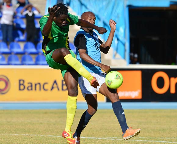Eridson Umpeca of Guinea Bissau clears from Lemponye Tshireletso of Botswana  during the 2015 African Cup of Nations football qualifier between Botswana and Guinea Bissau at the National Stadium in Gaborone on 19 July 2014