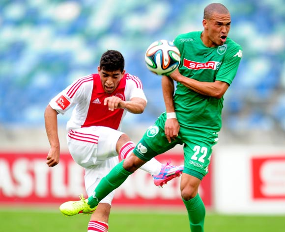 Travis Graham of Ajax Cape Town shoot past Ruzaigh Gamildien AmaZulu during the Absa Premiership 2014/15 football match between AmaZulu and Ajax Cape Town at the Moses Mabhida Stadium in Durban , Kwa-Zulu Natal on the 10th of August 2014